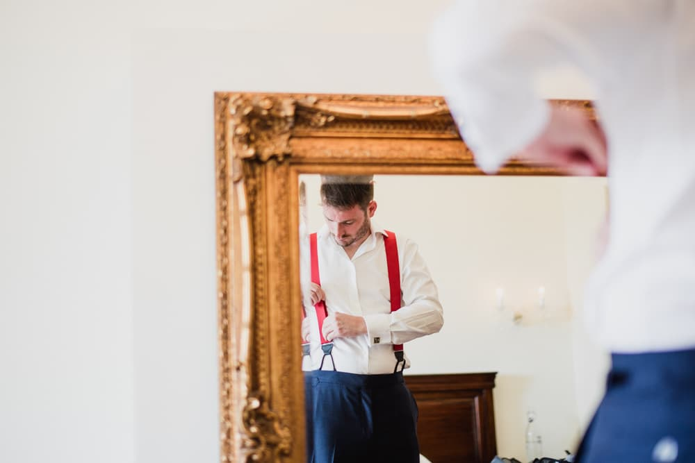 groom wearing red braces getting ready