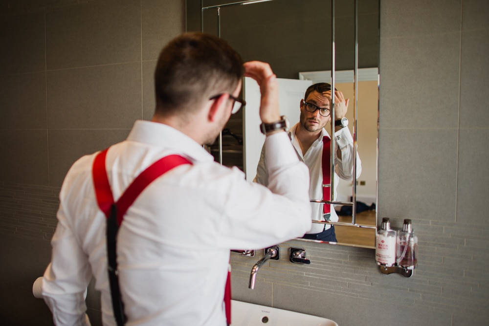 groom getting ready looking at reflection