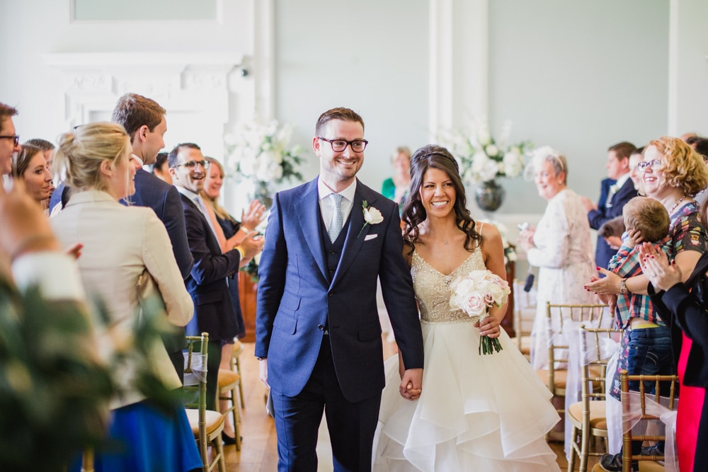 bride and groom walk down aisle together at Botleys Mansion