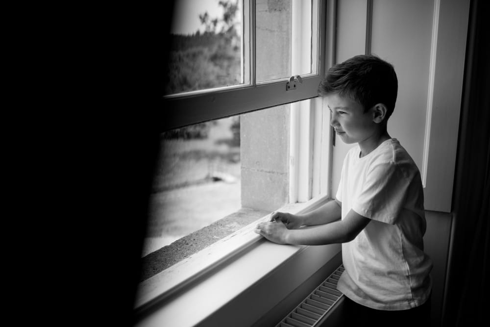 little boy looking out window at Botleys Mansion Surrey