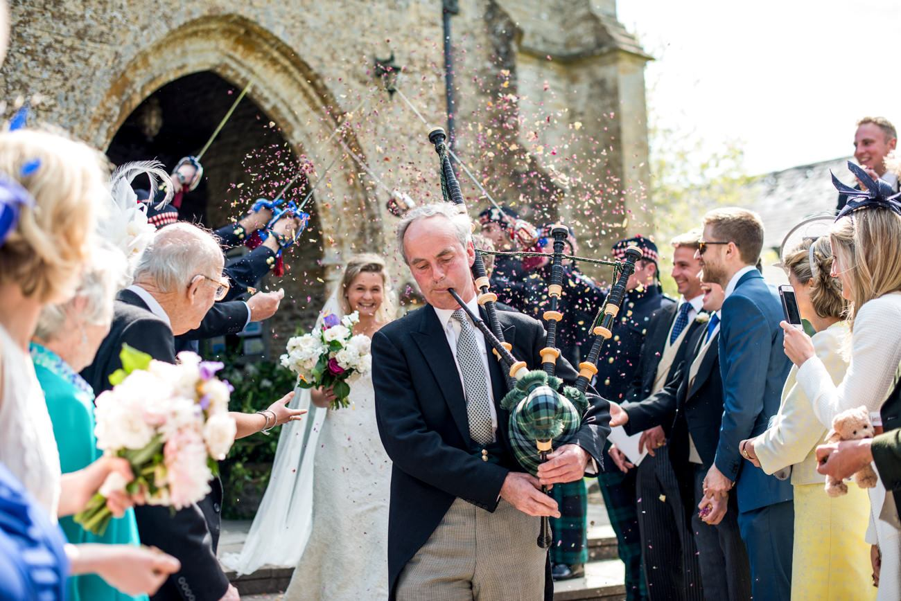 bride and groom lead out church with bagpipes