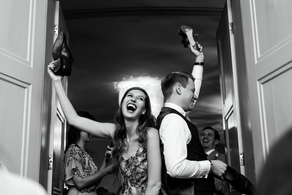 bride and groom holding up their shoes
