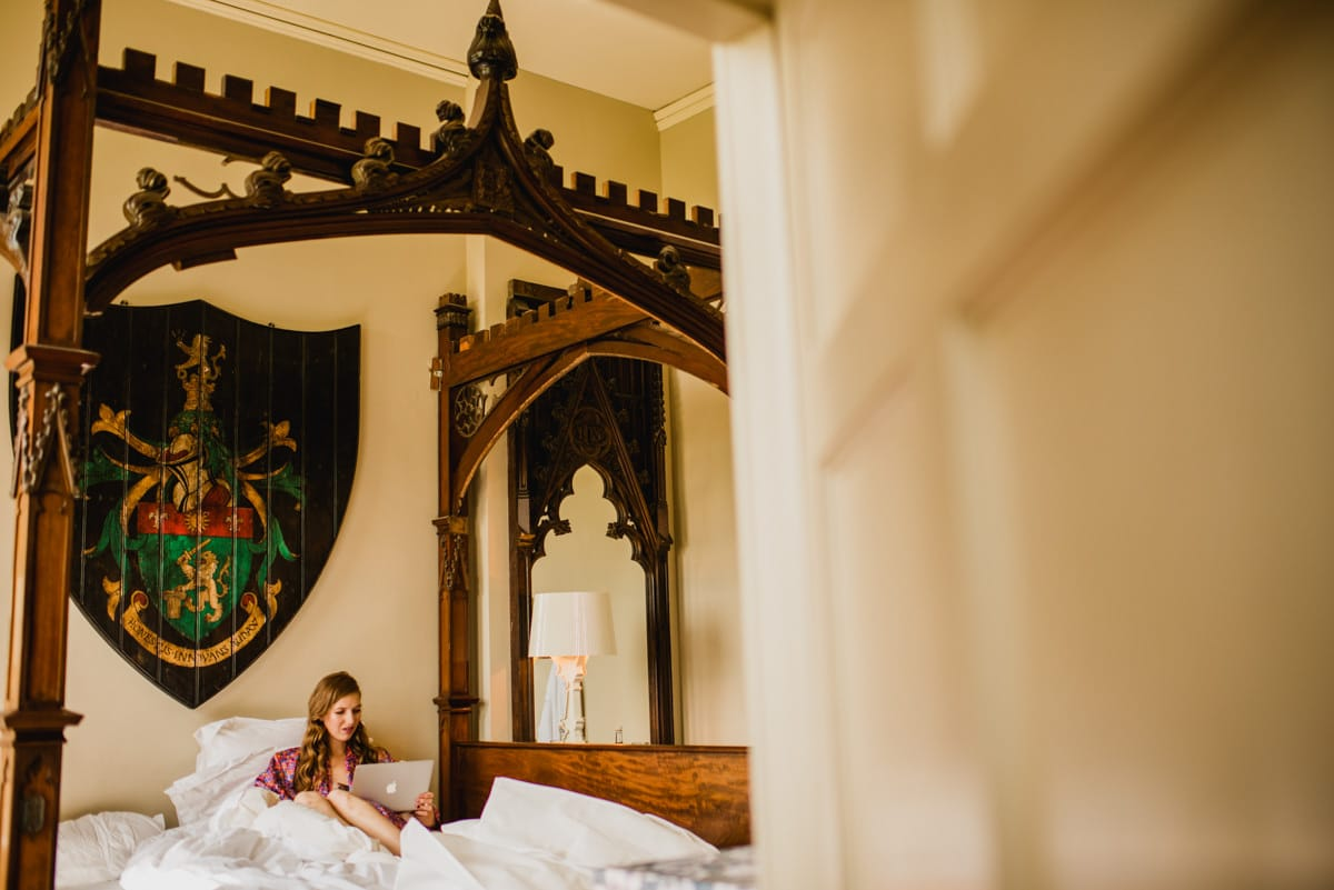 bride sitting in four poster best at Aynhoe Park