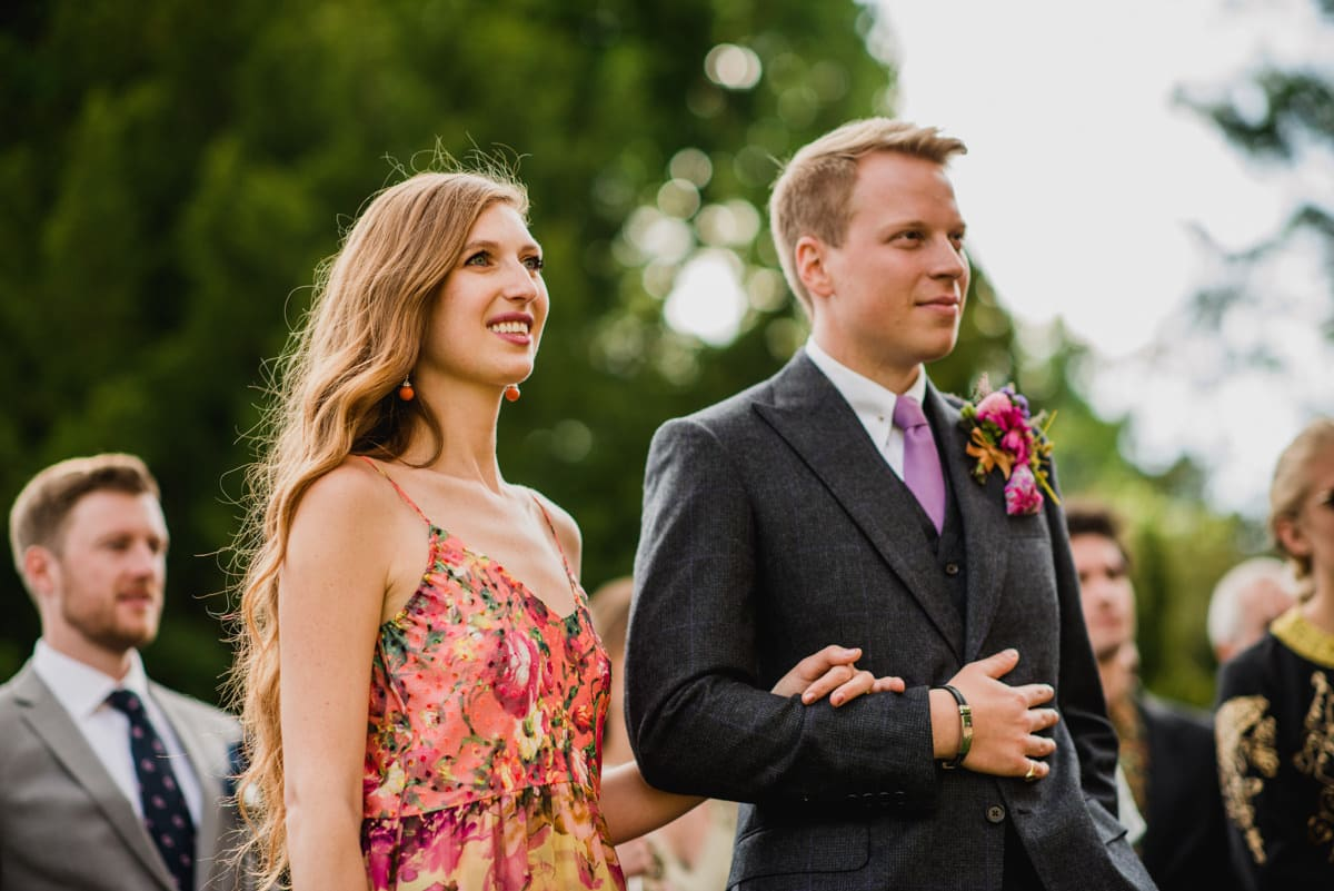 bride and groom listening to speeches outdoors