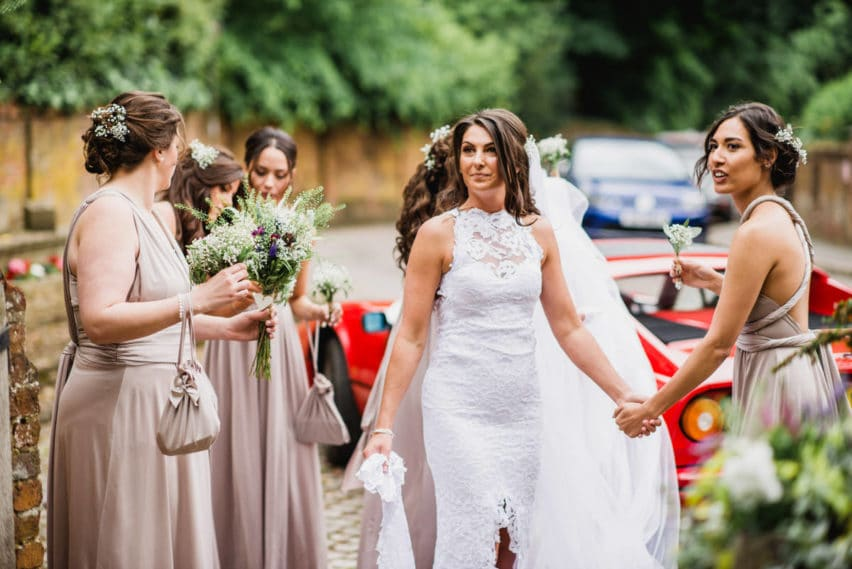 bride holding hands with bridesmaid