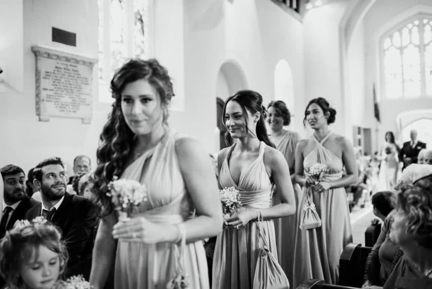 bridesmaids walking down the aisle in church