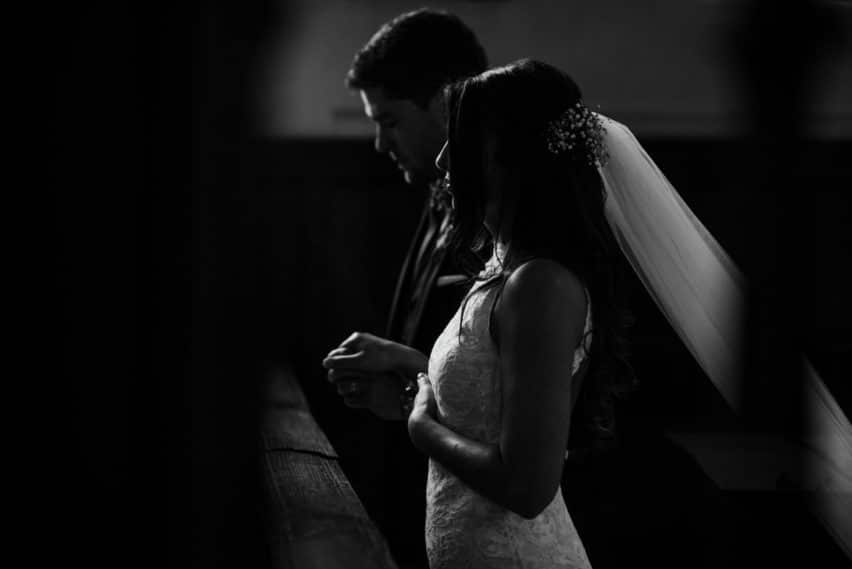bride and groom praying at alter