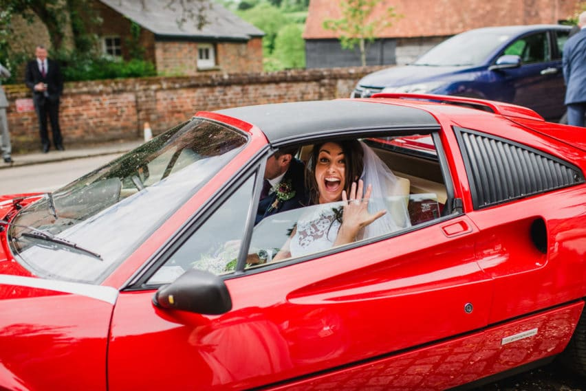 bride in Ferrari with ring hand up