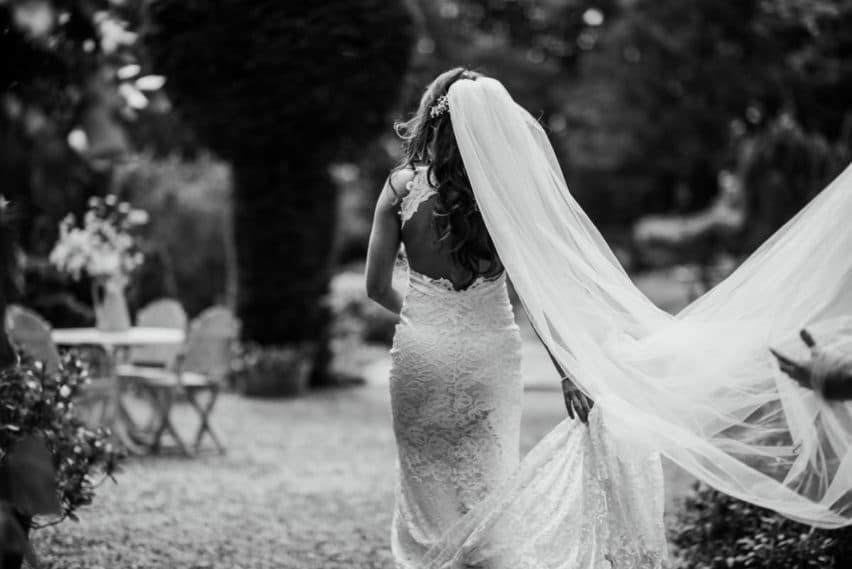 bride walking away with veil blowing in wind
