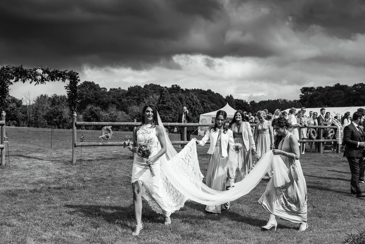 bride walking with bridesmaids holding her veil and train