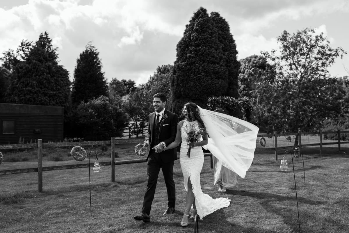 bride and groom walking together in wind