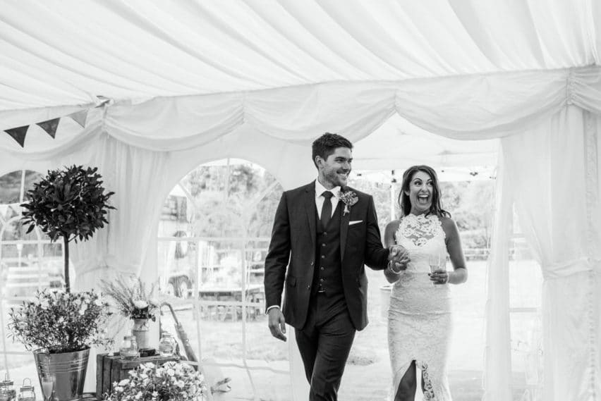 bride and groom walking into marquee