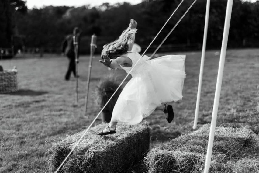 kids jumping on hay bails at wedding