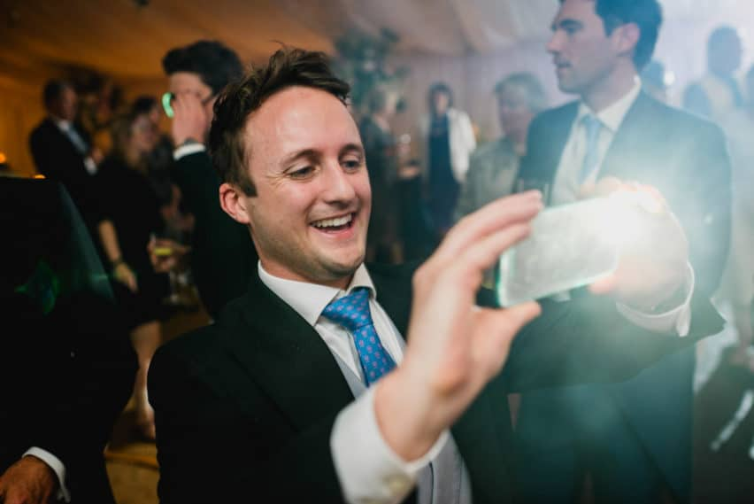 wedding guest taking picture on iPhone