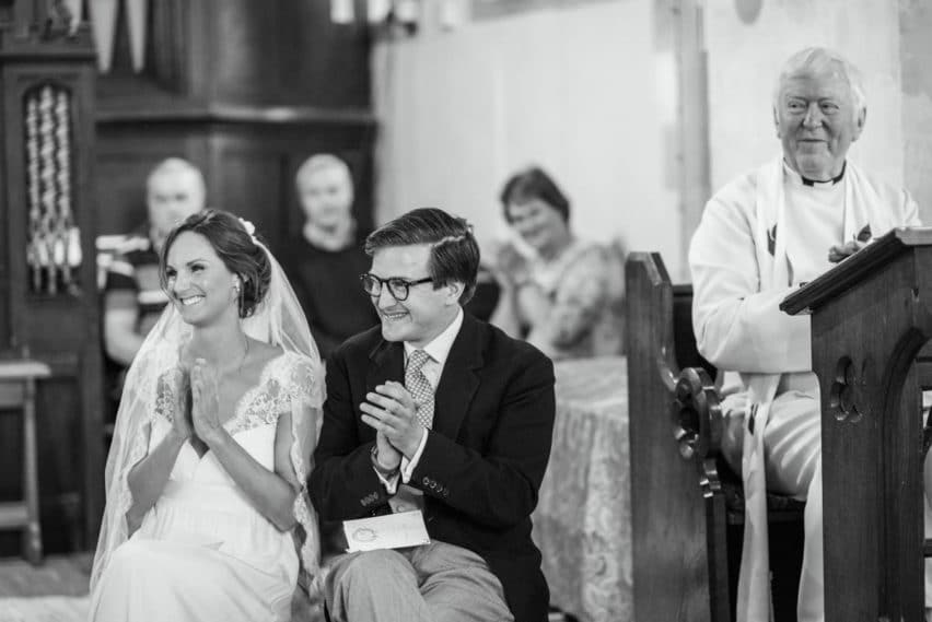 bride and groom clapping in church