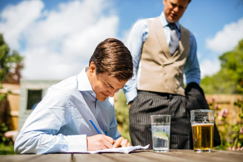groom writing speech at pub