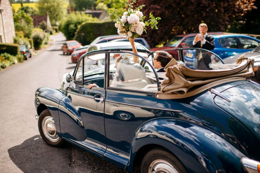 bride and groom leaving church in classic convertible