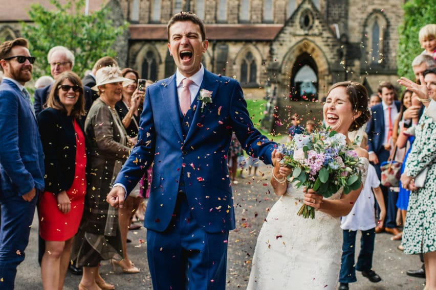 couple laughing walking through confetti outside church