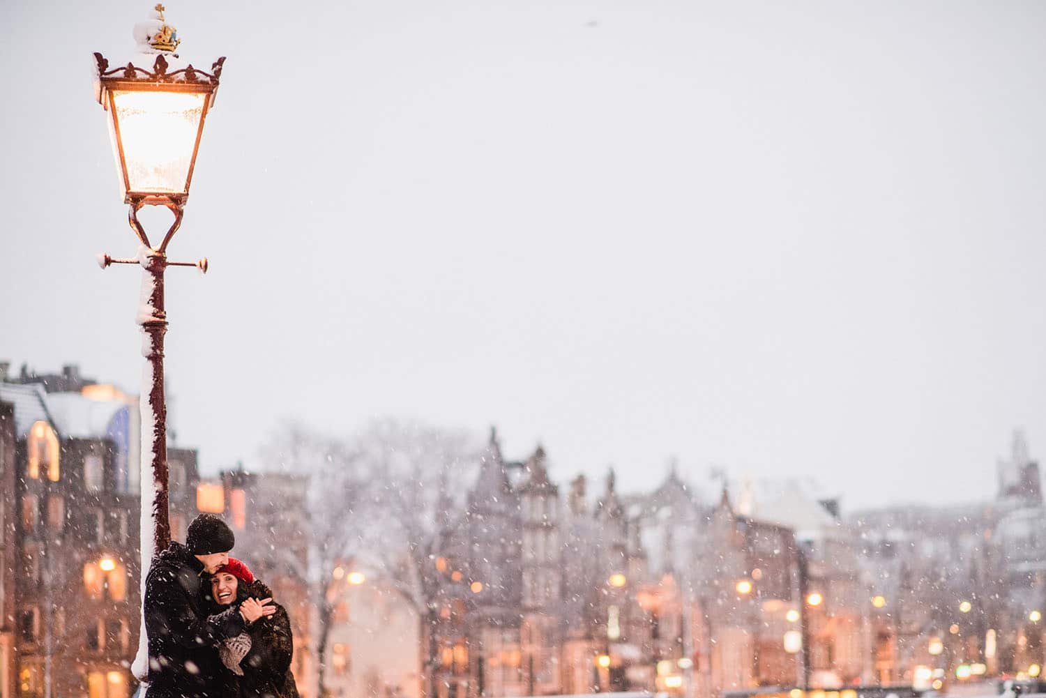 couple embracing under lamppost in snow