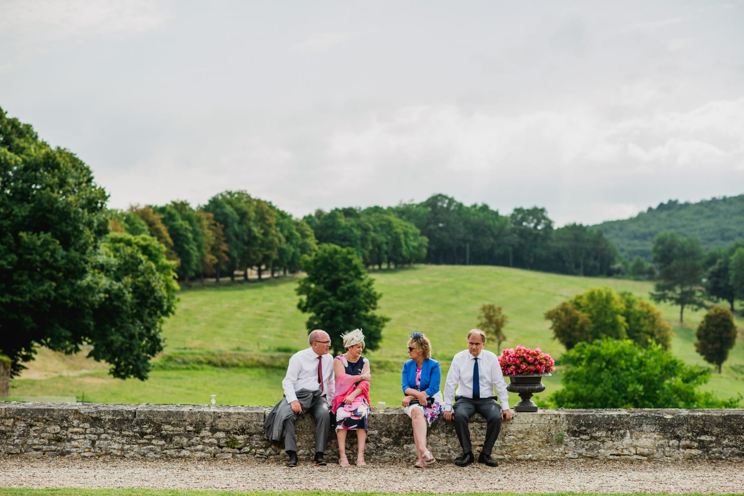 wedding guests sitting on wall