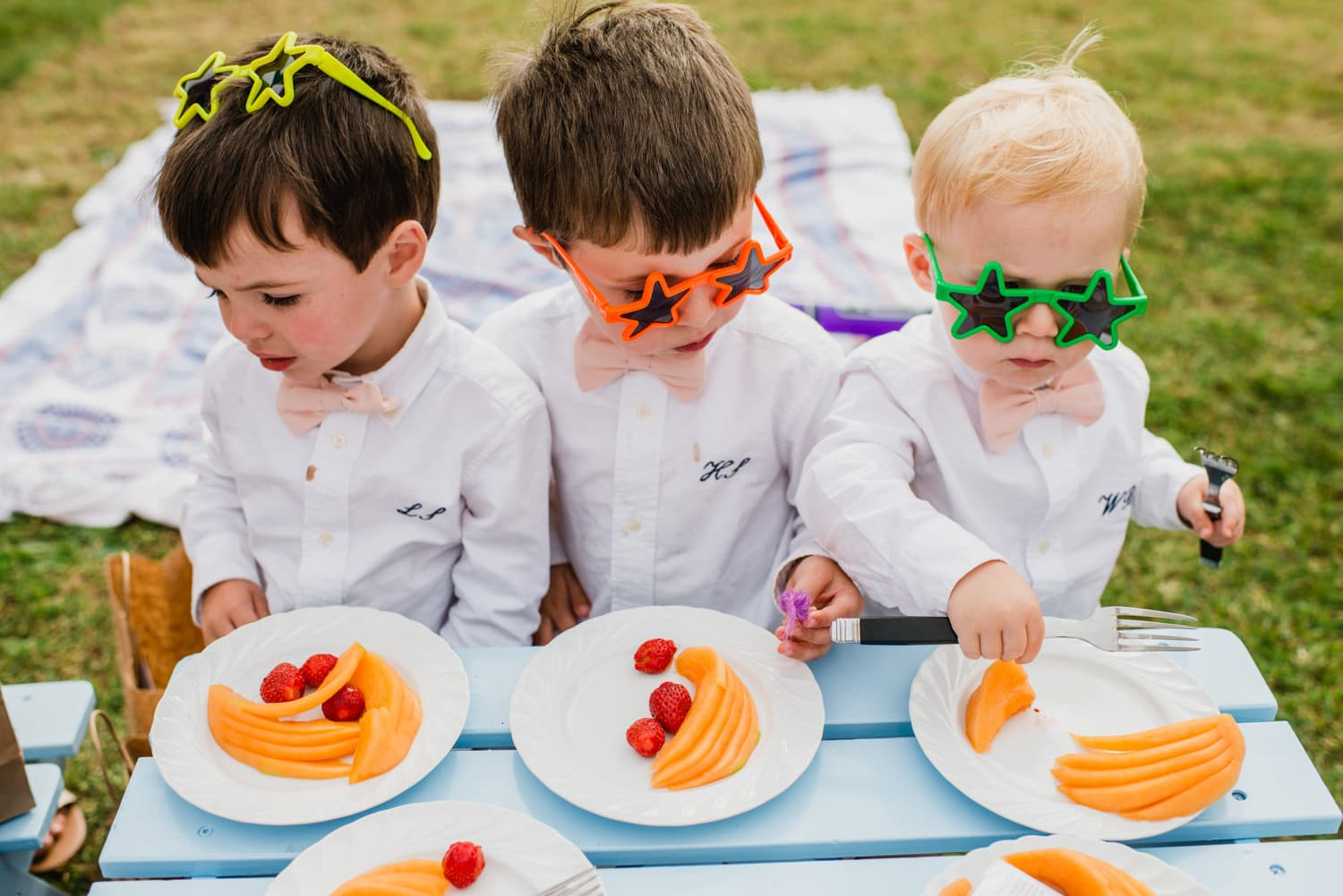 kids at wedding with star glasses sitting on blue picnic bench