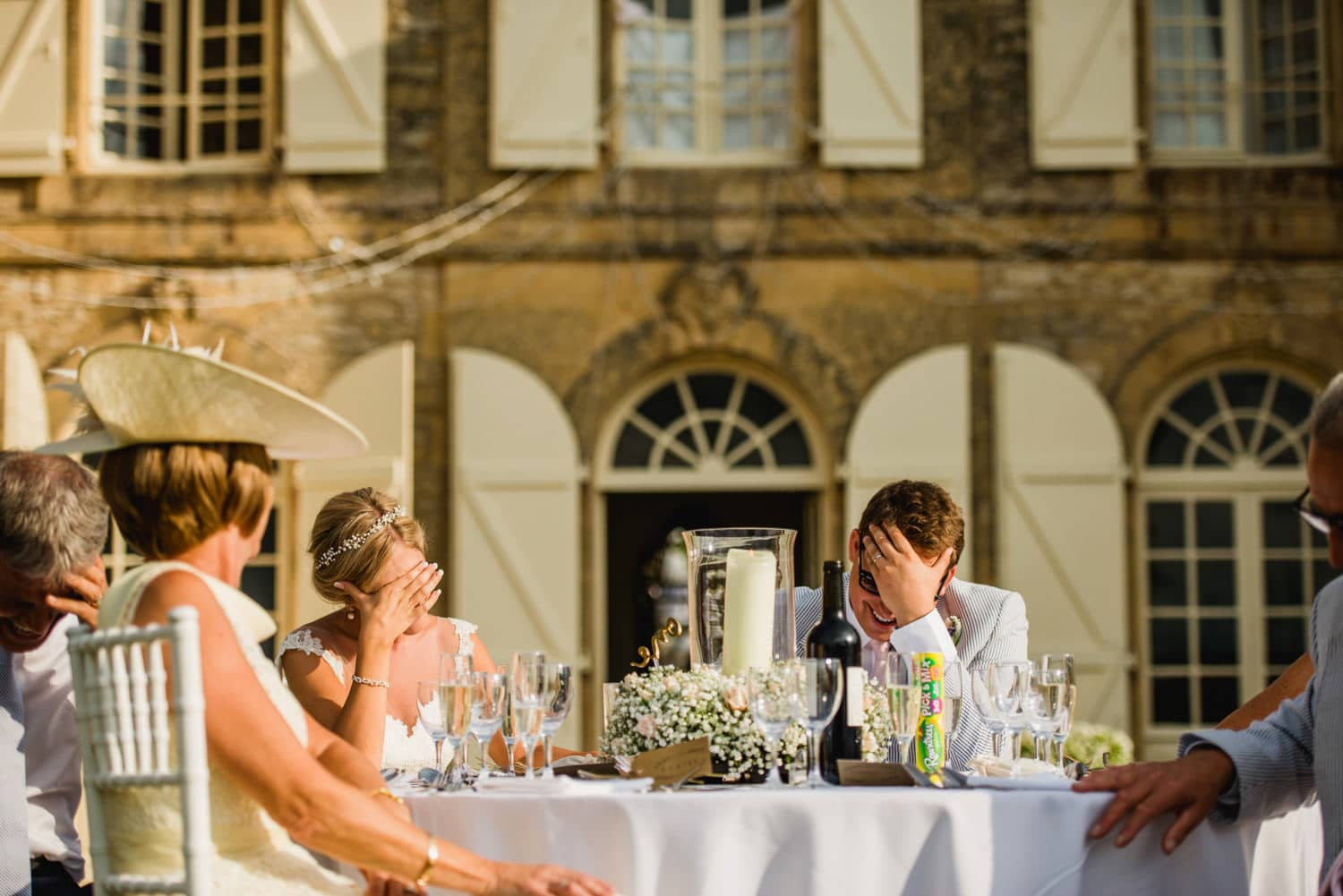 bride and groom with hands cover their faces during the speeches