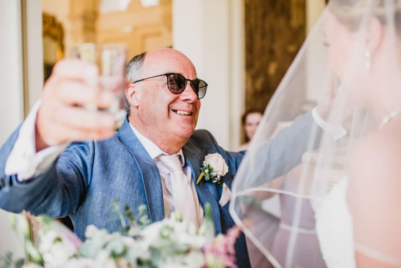 father of bride giving bride a hug
