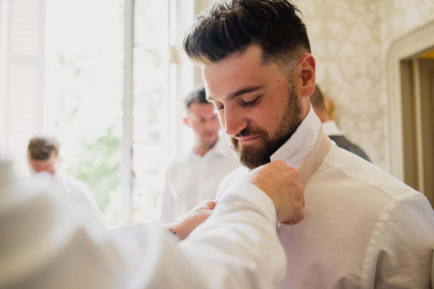 groomsmen putting ties on