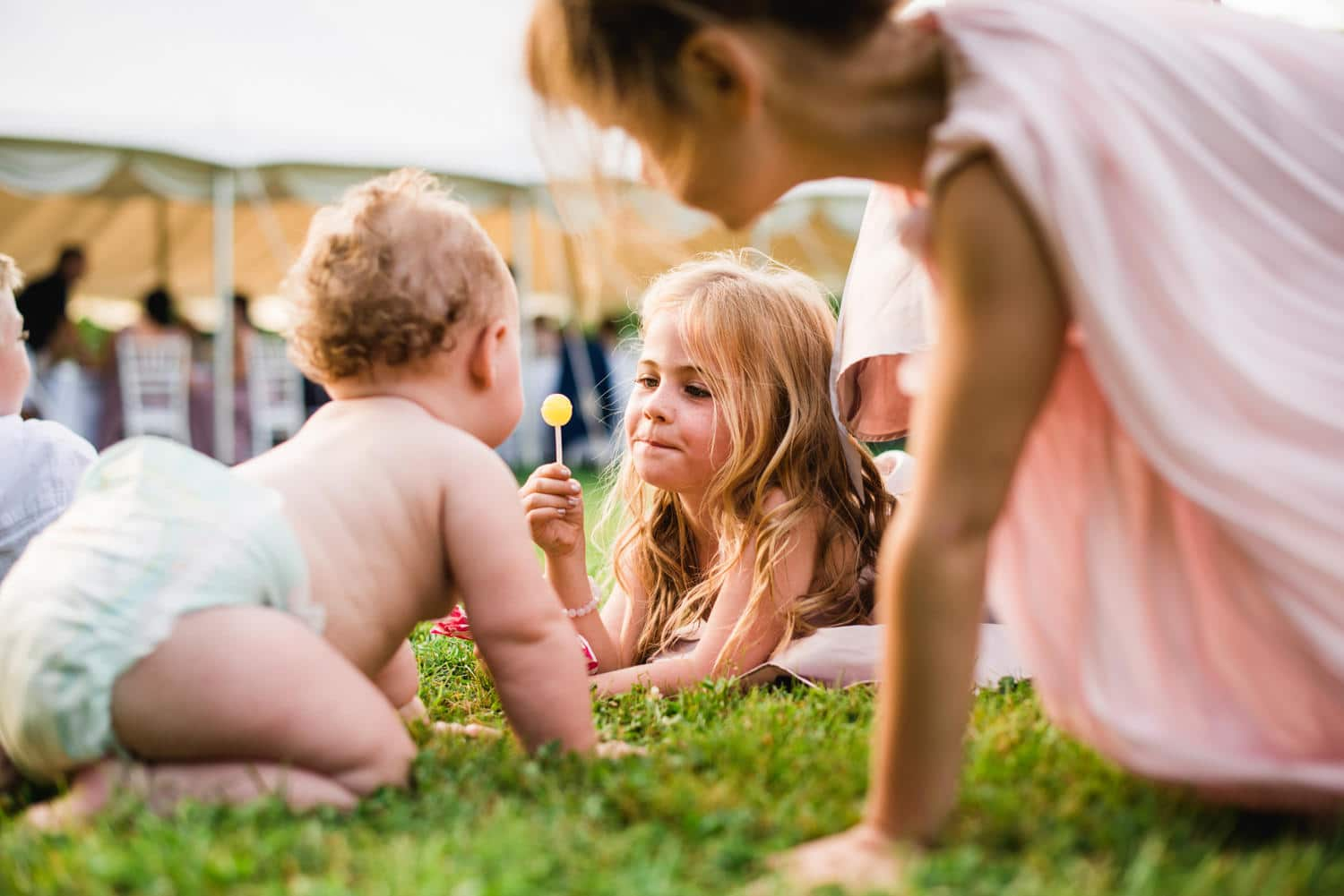 flower girl teasing baby with lollypop