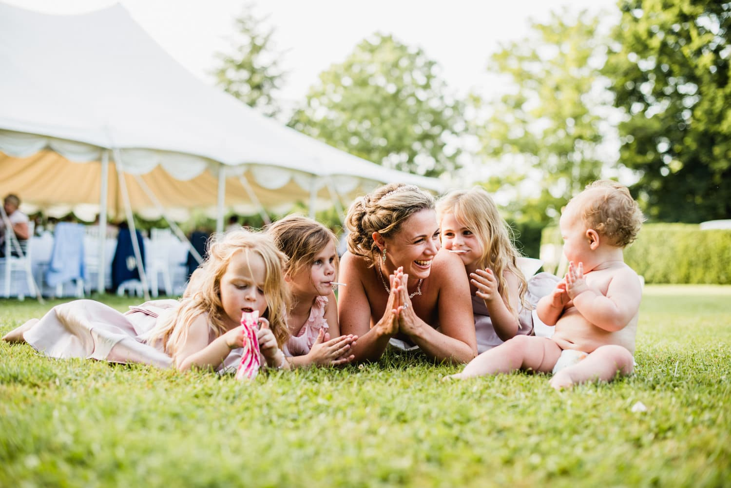 bride laying on grass with kids