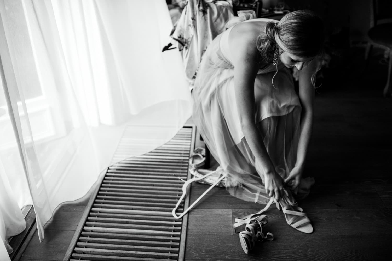 bridesmaid putting shoes on by window