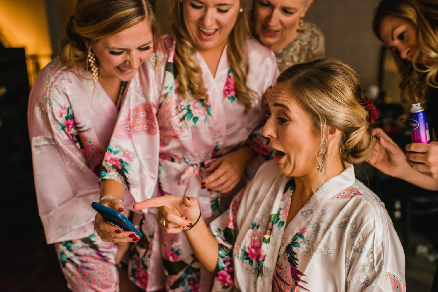 bride laughing at photo on phone