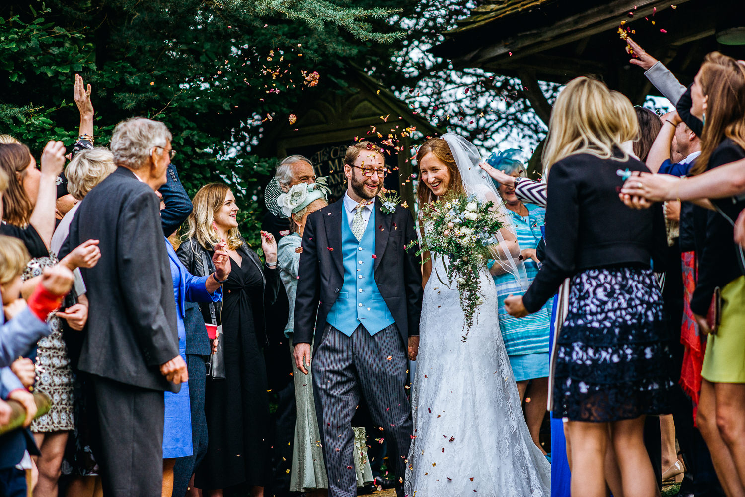 Bride and groom walking through confetti at wedding in Hampshire