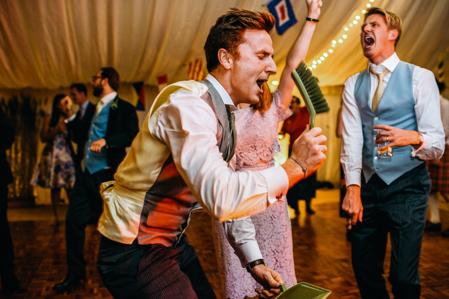 Wedding Guest singing into dust pan and brush