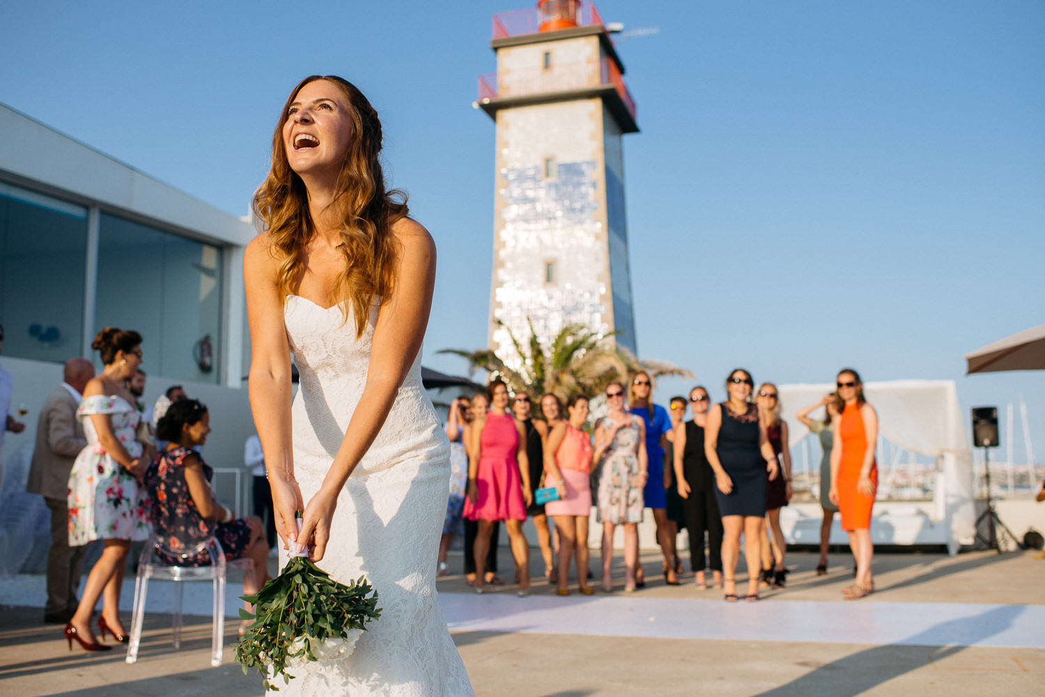wedding venue with lighthouse, bride throwing bouqet