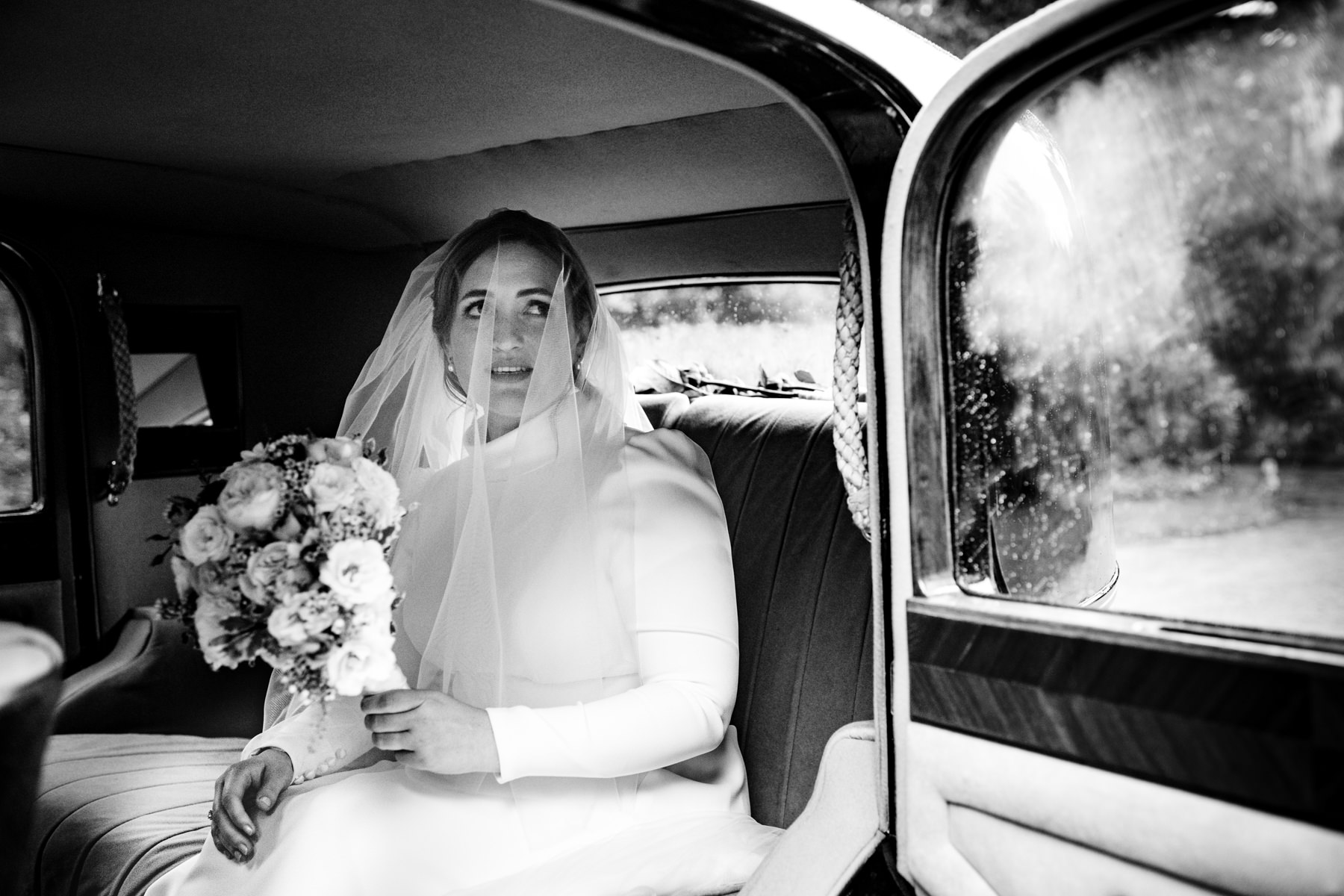 bride in wedding car with misted up windows