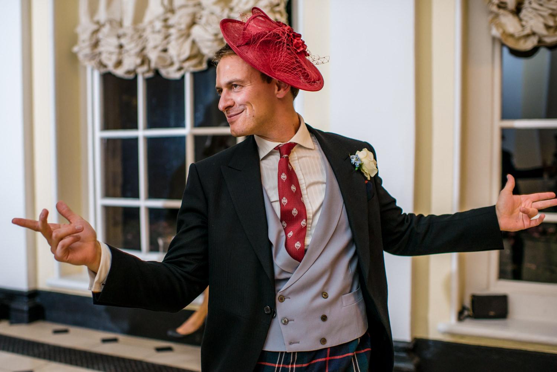 male wedding guest wearing red wedding hat