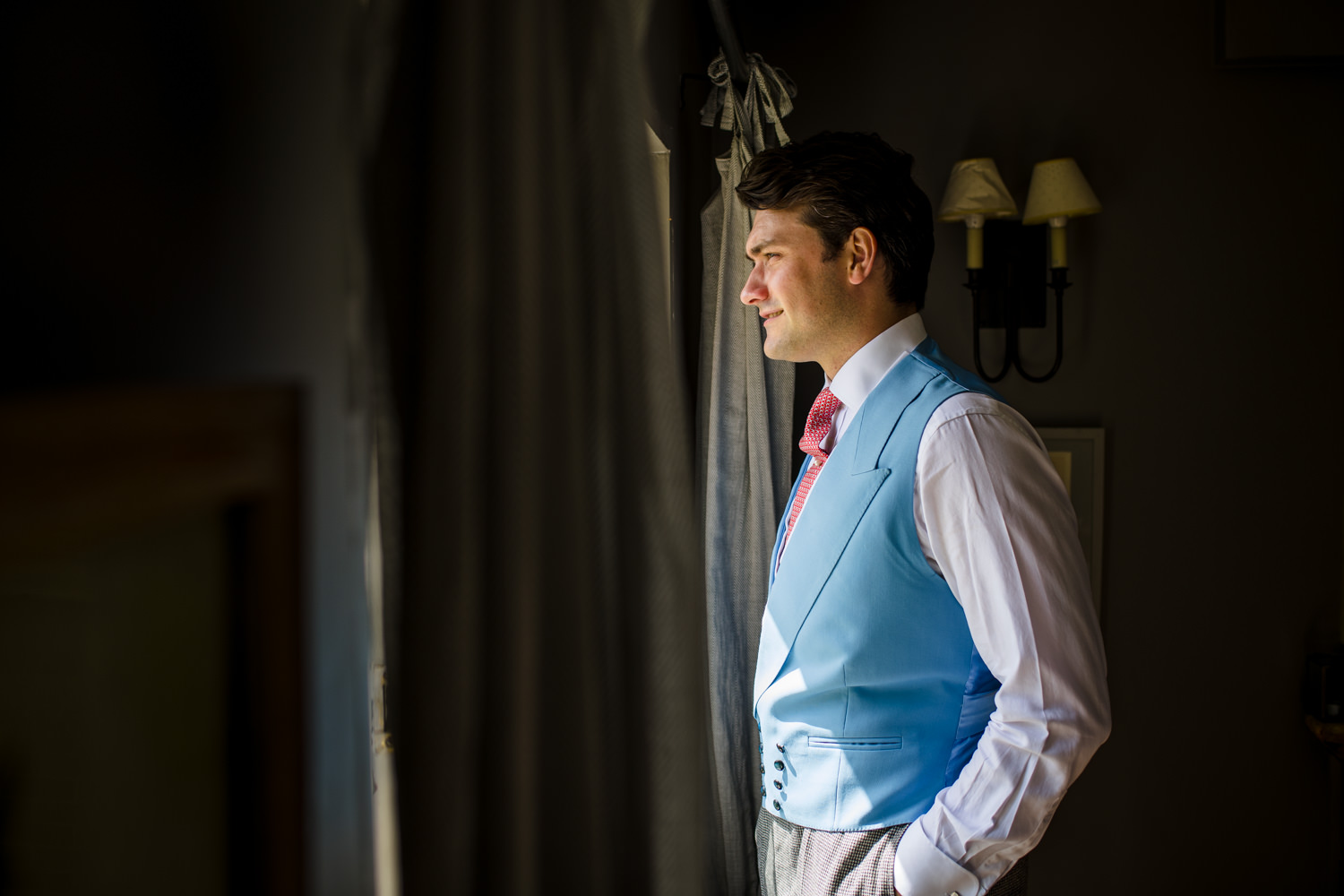 groom in pink and light blue waistcoat looking out window